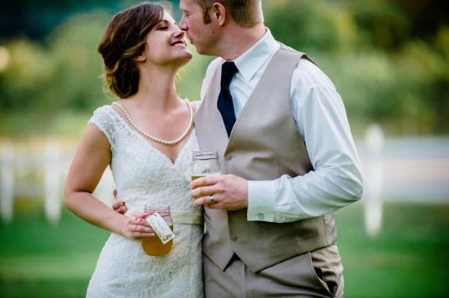 Bride and groom holding mason jars as drink glasses and about to kiss