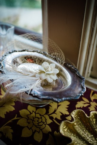 Birdcage veil with flower and feathers sitting on silver plate