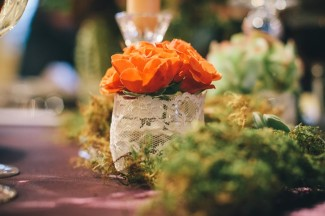 Small vase wrapped in lace with orange roses inside