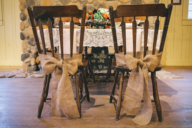 Two rustc chairs with burlap bow for rustic fall table setting