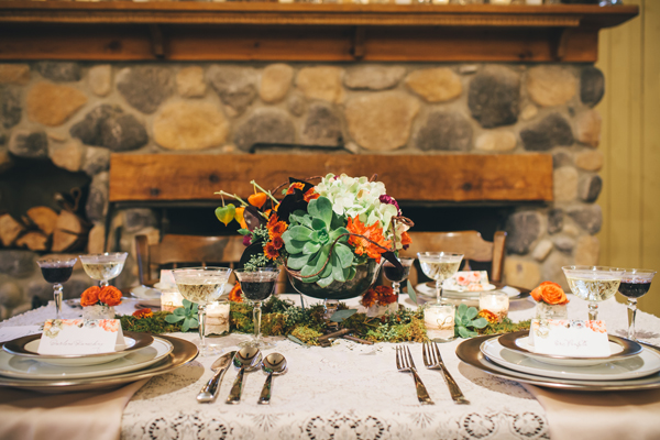 Lace tablescape with moss, vintage keys, succulents and orange flowers in front of a fire place