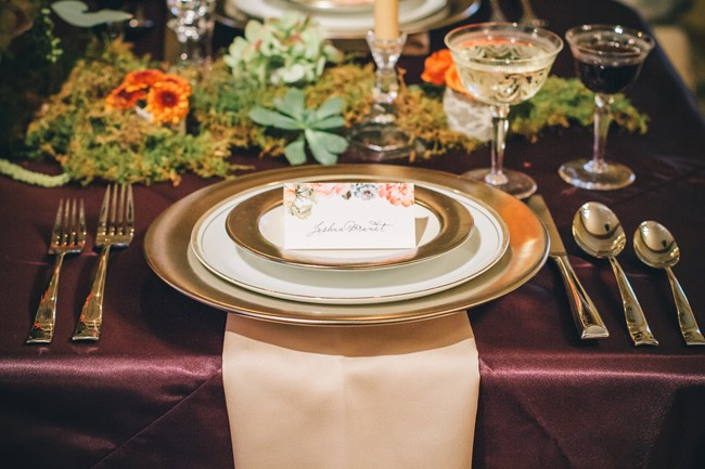 Wedding reception place setting with fall theme. Gold, purple and orange colors