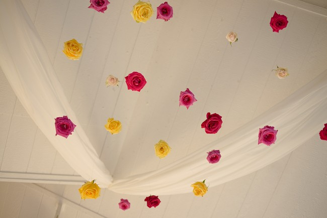 Yellow and pink flowers on stings hanging from the ceiling as wedding decor