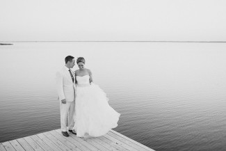 black and white photo of bride and groom standing on a wooden dock at Sanderling Resort