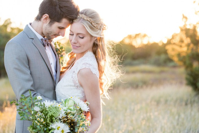 bride and groom standing together in field.  Bride holding wild flower bouquet and braid in her hair.
