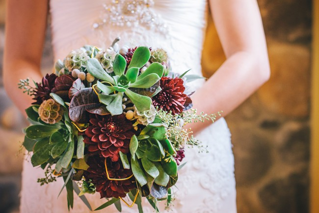 bride holding purple, orange, yellow bouquet with succulents
