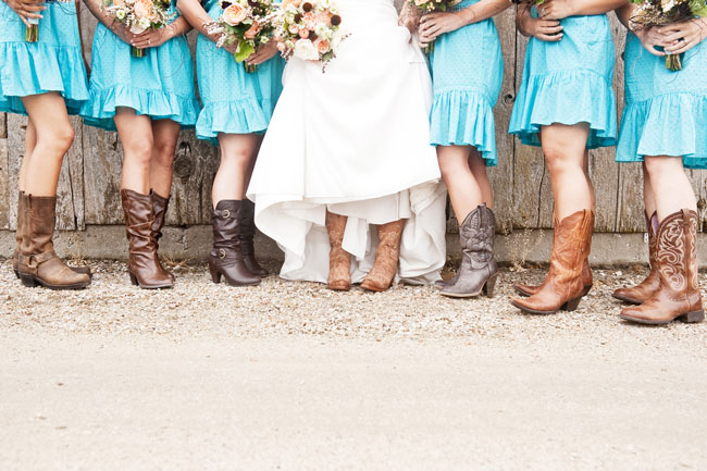 Bride wearing cowboy boots standing with bridesmaids wearing brown colored cowboy boots and teal knee length dresses.