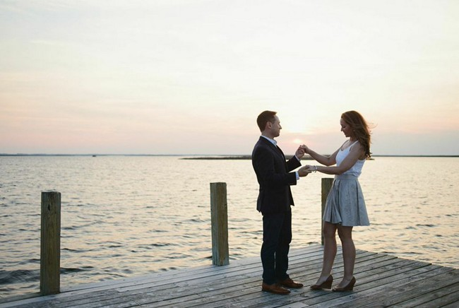 engaged couple holding hands on a dock