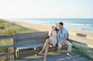 engaged couple sitting on a bench at the beach