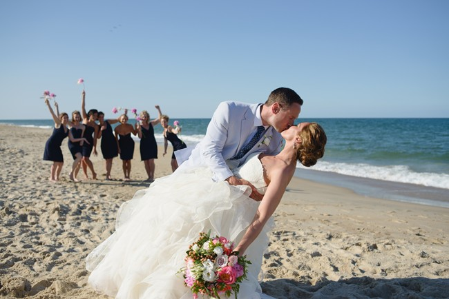 groom giving bride a kiss on the beach with bridesmaids cheering in the back ground