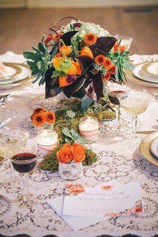 lace table cloth with floral center pieces of orange, purple, green colored flowers and white candles