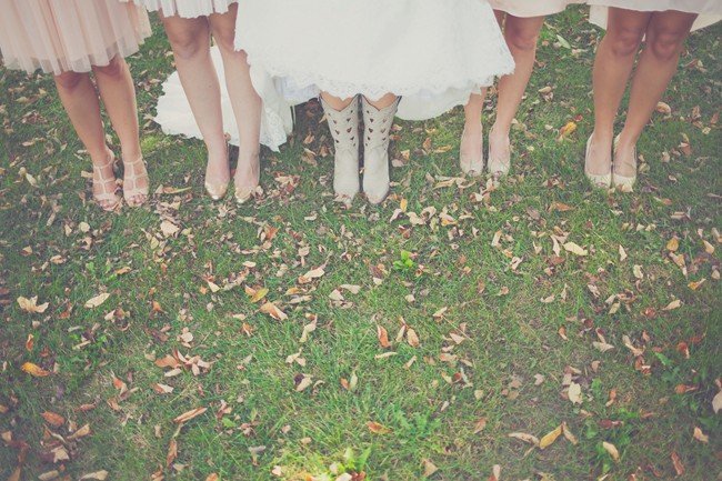 Bride wearing light colored cowboy boots with heart cut outs, standing with bridesmaids wearing nude heels