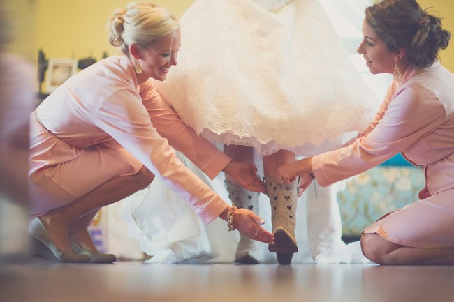 Bridesmaids helping bride put on light colored cowboy boots with heart cut outs on