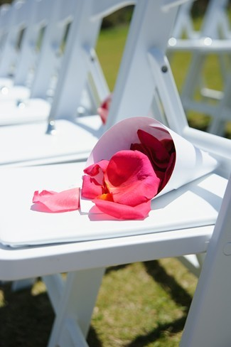 pink petals in a cone on a white chair before wedding ceremony