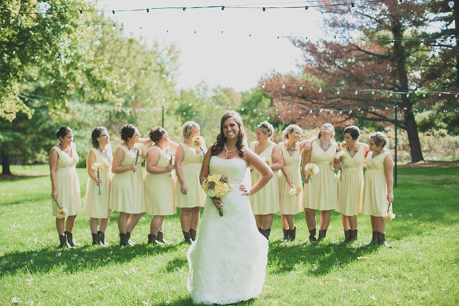 Bride posing in front of bridesmaids who are lined up behind her wearing short ankle cowboy boots and yellow knee length dresses.