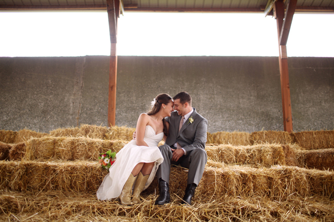 Bride and groom sitting head to head on a hay stack. Bride wearing light brown colored cowboy boots.