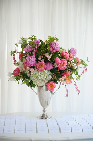wedding escort cards lined on a table with a silver vase full of pink, white, red, green flowers
