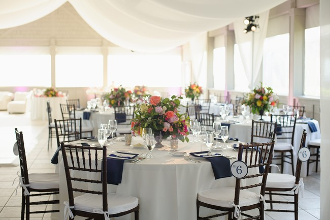 wedding reception at Sanderling Resort with white table cloths, navy blue napkins, brown chevalier chairs