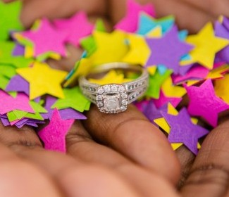 princess cut double halo diamond ring in hands with colored paper stars