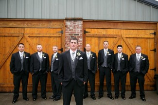 Groom with groomsmen wearing grey vests and plaid neck ties