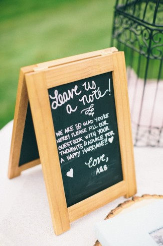 Chalkboad sandwhich sign asking guests to leave the bride and groom a note