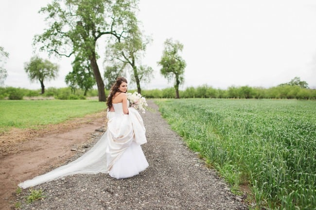 bride standing on trail in field holding up dress and wearing a chapel length veil