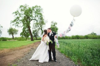 bride and groom standing on trail in field kissing while holding a white geronimo balloon