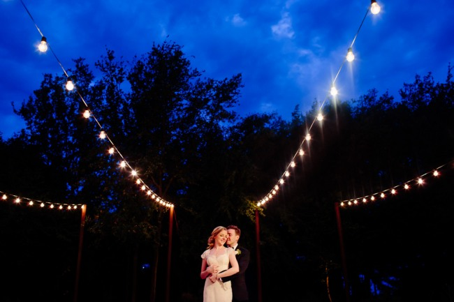 couple dance under outdoor string lighting