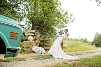 Groom dunking bride and kissing her outside on farm with blue truck in the corner