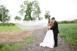 Bride and groom embracing on trail in field while brides chapel length veil blows in the wind