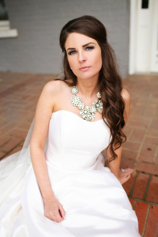 bride sitting on red brick stairs wearing hair half up, strapless dress and chunky necklace