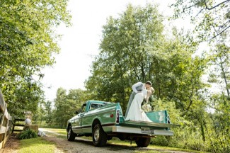 Groom dunking bride while kissing her on the bed of a blue vintage truck