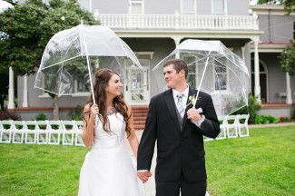 Bride and groom in front of Patrick Ranch Museum each holding bubble umbrella
