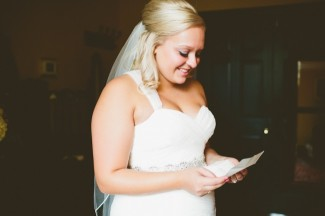 bride smilling while reading note from groom before ceremony
