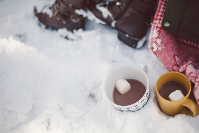 2 mugs sitting in the snow with hot chocolate inside and floating marshmellow