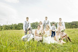 Bride and groom with bridal party sitting on a vintage couch out in a field