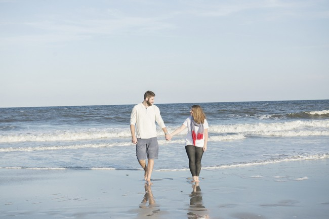 Couple walking on beach away from the shoreline