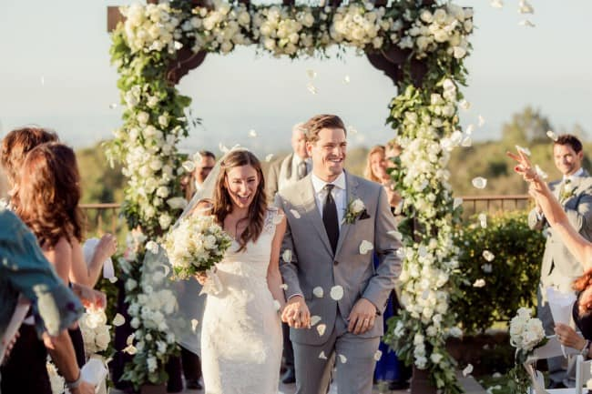 20 bride and groom walking down aisle while guest throw rose petals in the air