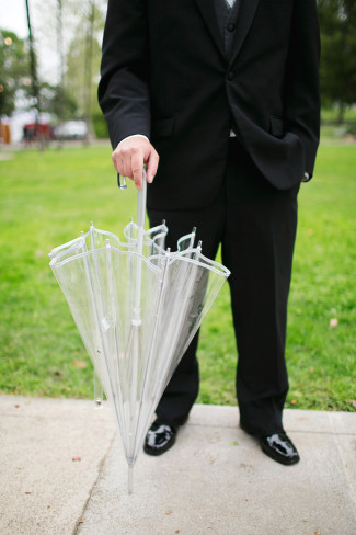 groom holding clear plastic umbrella