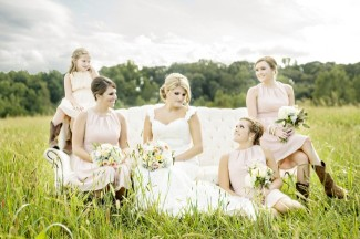 Bride with bridal party wearing cow boy boots sitting on vintage sofa out in a grass field