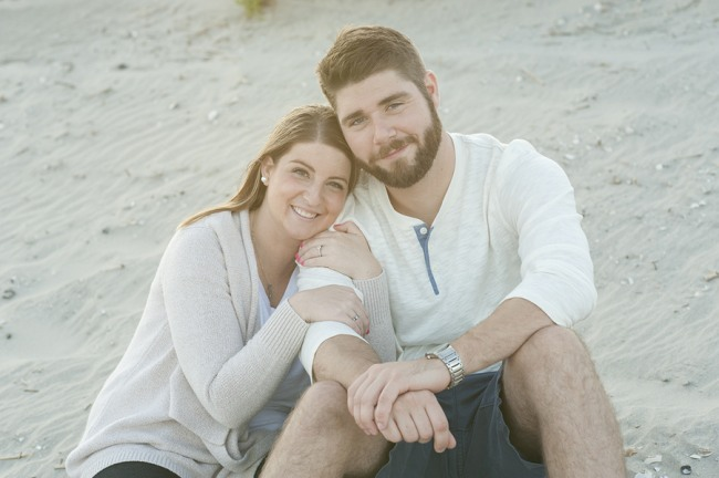 Couple sitting on a beach for an engagement shoot