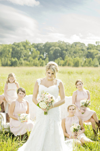 bride with bridal party sitting out in a grass field holding pink and white bouquets