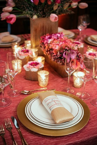 22 pink table cloth with gold charger place setting with gold napkin folded in the center