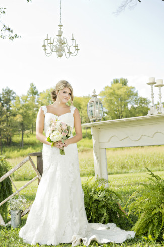 bride posing at wedding ceremony altar under chandelier and fake fireplace mantel for outdoor wedidng