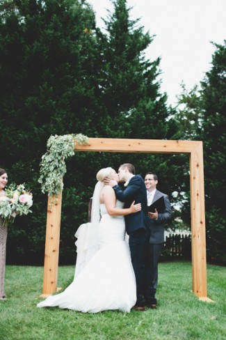 Bride and groom kissing during outdoor ceremony in front of wood square arch alter