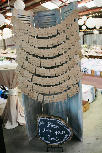 rustic escort cards hanging from shutters for wedding reception