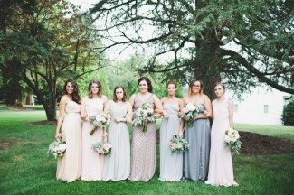 Bridesmaids wearing floor length mis matched gowns all in grey, purples and pinks