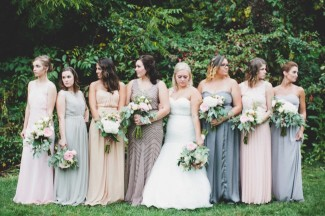 Bride standing with bridesmaids wearing mismatched floor length gowns in grass
