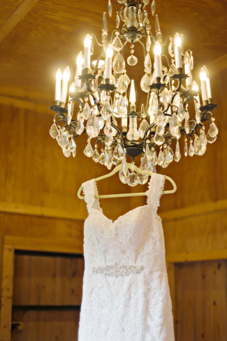 lace wedding gown hanging from a chandelier