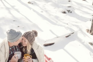 3 couple sitting in white snow in the forest drinking hot chocolate